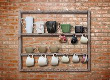 Viel Kaffeetasse auf hölzernem Regal Lizenzfreie Stockfotos