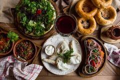 Viel Lebensmittel auf dem Holztisch Georgische Küche Beschneidungspfad eingeschlossen Flache Lage Khinkali und georgische Teller Stockfotos