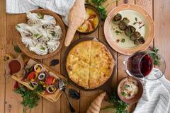 Viel Lebensmittel auf dem Holztisch Georgische Küche Beschneidungspfad eingeschlossen Flache Lage Khinkali und georgische Teller Stockbild