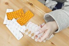 Viel Medizin auf Nachttabelle im Schlafzimmer Frau, die eine Medizin nimmt Lizenzfreie Stockfotos