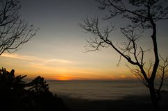 Viel Nebel und Sonnenaufgang hinter dem Berg Stockfotografie