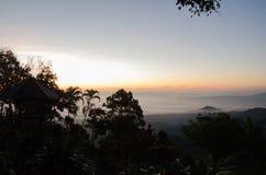 Viel Nebel und Sonnenaufgang hinter dem Berg Stockfoto