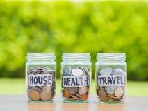Viel rütteln Münzen im Glasgeld auf der hölzernen Tabelle Einsparung für Haus lizenzfreies stockbild