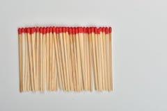 Viel rotes Hauptmatch setzte sich gerade in Linie auf weißen Hintergrund Lizenzfreie Stockfotos