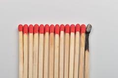 Viel rotes Hauptmatch und eins gebrannt gerade eingegeben in Linie auf whi Lizenzfreie Stockfotos