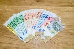 viel verschiedene Eurobanknote und Münzen auf Holz Stockbilder