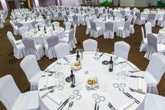 Viel von großen Rundtischen und die Stühle, die mit weißer Tischdecke bedeckt werden, werden für eine Mahlzeit im Restaurant Gork Lizenzfreie Stockbilder