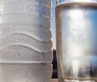 Viel Wasser fällt auf die Flasche mit Wasser und Glas Stockbilder