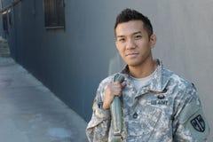 Vieldeutiger amerikanischer Soldat der Junge ethnisch, der Rucksack hält Lizenzfreie Stockfotografie