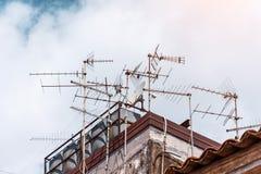 Viele Antennen des Satelliten- und analogen Fernsehens auf dem Dachgebäude stockfotografie
