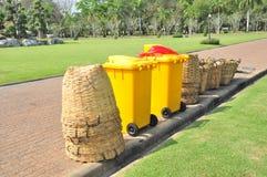 Viele Arten Behälter wie Bambuskörbe, gelbe fahrbare Behälter stehen am Rand der Wegweise für halten einen Abfall Lizenzfreie Stockfotos