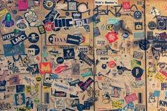 Viele Aufkleber von alten Logos auf einer Wand des Gebäudes Lizenzfreie Stockfotos