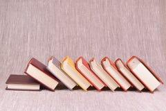 Viele Bücher auf einem Leinenhintergrund Stockbilder