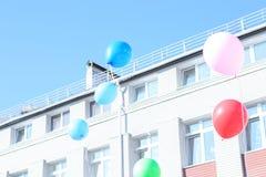 Viele Ballone fliegen in den blauen klaren Himmel und errichten auf dem Ba lizenzfreies stockbild