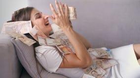 Viele Banknoten fliegen in die Luftunkosten in der Zeitlupe Ein M?dchen liegt und viele Geldf?lle auf sie gl?ckliche Frau freut s lizenzfreie stockfotos