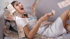 Viele Banknoten fliegen in die Luftunkosten in der Zeitlupe Ein M?dchen liegt und viele Geldf?lle auf sie gl?ckliche Frau freut s lizenzfreie stockbilder