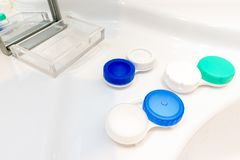 Viele Behälter und ein Kasten mit Spiegel für Kontaktlinsen stockfotografie