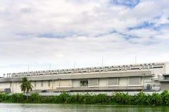 Viele Belüftungskamine auf dem Fabrikdach am blauen Himmel und an den Wolken mit Kopienraum stockfoto