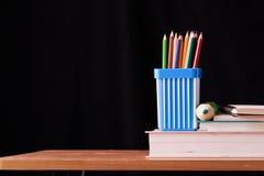 Viele Bleistifte im Metallhalter auf Holztisch auf schwarzem Bretthintergrund Stockfotografie