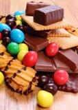 Viele Bonbons auf Holzoberfläche, ungesundes Lebensmittel Stockfotografie