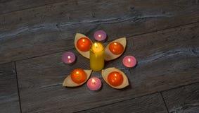Viele brennende gelbe, orange und weiße Kerzen Stockbild