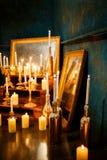 Viele brennende Kerzen auf einem widergespiegelten Hintergrund Stockfoto