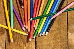 viele bunten Bleistifte auf altem Holztisch Stockbild