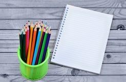 Viele bunten Bleistifte mit leerem Notizbuch Lizenzfreies Stockfoto