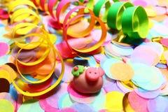 Viele bunten Confettis, Papierschlangen und ein Marzipanschwein stockbilder