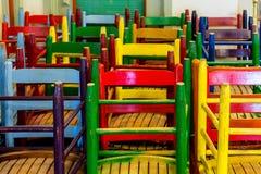 Viele bunten hölzernen Stühle Stockbilder