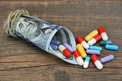 Viele bunten Pillen und Kapseln fallen gelassen von der Geld-Rolle Stockbild