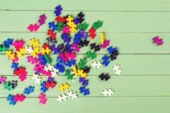 Viele bunten Puzzlespiele auf Holztisch Lizenzfreie Stockbilder