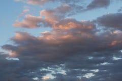 Viele Cumulonimbuswolken im blauen Himmel, Sonnenuntergang strahlt die weißen und grauen Wolken der Farbe in der leichten rosa Fa Stockfotografie