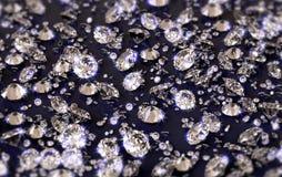 Viele Diamanten auf einer glatten reflektierenden Fläche mit blauer Tönung, mit Schärfentiefe stockfoto