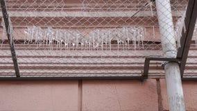 Viele Eiszapfen auf einem Metallsicherheitsgitter der Fassade des Gebäudes Stockbild