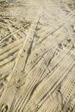 Viele ermüden Bahnen und Abdrücke in den verschiedenen Richtungen auf den Strandsand Lizenzfreies Stockfoto