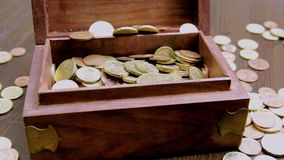 Viele Euromünzen in der Holzkiste auf weißem Abwehrgeld stock footage