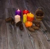 Viele farbigen Kerzen und Kegel auf altem hölzernem Hintergrund Lizenzfreie Stockfotos