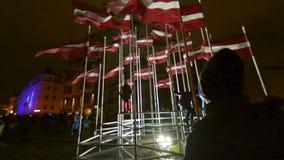 Viele Flaggen von Lettland auf 18 des November-Tagesfeier-Lichtfestivals Staro Riga stock video