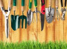 Viele Gartenarbeitwerkzeuge auf hölzernem Hintergrund stockfotos