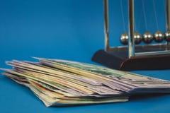viele Gelddollar und Newtonb?lle auf einem blauen Hintergrund lizenzfreie stockfotos