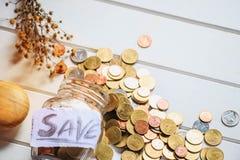 Viele Geldmünzen in der Glasflasche lizenzfreie stockfotos