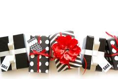 Viele Geschenkboxen im Schwarzweiss-Packpapier Rot und silve Stockbilder