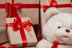 Viele Geschenke, Kästen mit den Geschenken bedeckt mit rotem Satin und Seidenband mit großem Bogen, frohe Weihnachten und ein gut Lizenzfreies Stockbild