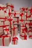 Viele Geschenke, Kästen mit den Geschenken bedeckt mit rotem Satin und Seidenband mit großem Bogen, frohe Weihnachten und ein gut Stockbild