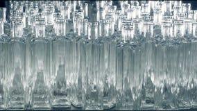 Viele Glasflaschen werden auf ein Fließband in einer Anlage gesetzt 4K