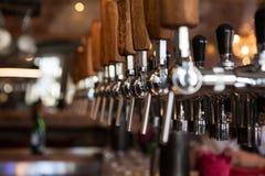Viele goldenen Bierhähne an der Bar Lizenzfreie Stockfotos
