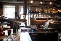 Viele goldenen Bierhähne an der Bar Lizenzfreie Stockfotografie