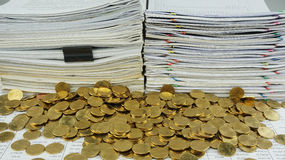Viele Goldmünzen vor Dokumenten lizenzfreies stockfoto