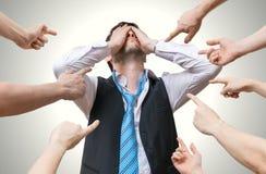 Viele Hände, die auf enttäuschten Mann zeigen und tadeln ihn Stockfotografie